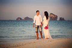 bride and groom walk  at  beach at dawn Royalty Free Stock Photo