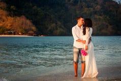 bride and groom walk at beach at dawn Stock Images