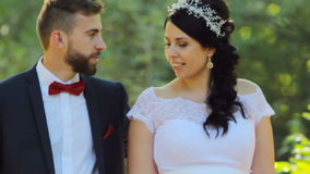Bride and groom walk in beautiful park stock video footage