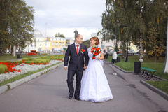 Bride and groom walk in city park Stock Photography