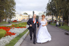 Bride and groom walk in city park Royalty Free Stock Image