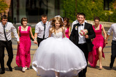 Bride and groom walk in the park being followed by their friends Royalty Free Stock Photography