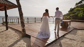 The bride and groom walk together holding hands on the hotel`s terrace overlooking the ocean. From the height of the stock video footage