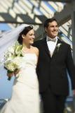 Bride and groom walking. Caucasian mid-adult bride and groom walking together smiling Stock Images