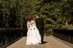 Bride and Groom Walking Across Bridge. A young bride and groom walk away across an old wooden bridge Stock Photo