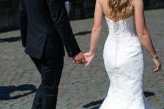 Bride and groom walking along the stony street Royalty Free Stock Photography