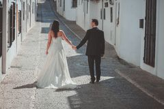 Bride and groom walking along the street stock photography