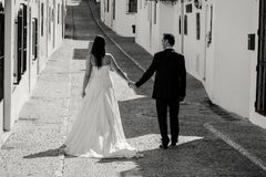 Bride and groom walking along the street royalty free stock photo