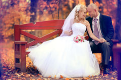 Bride and groom walking in autumn park Stock Photography