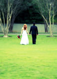 Bride and groom walking away, cross process, blur Stock Photos
