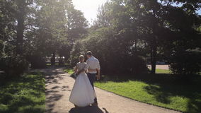 Bride and groom walking away in park outdoors stock video footage