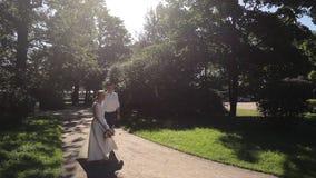 Bride and groom walking away in park outdoors stock video