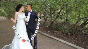 Bride and groom walking away in summer park. Outdoors stock footage