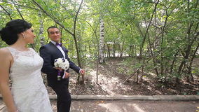 Bride and groom walking away in summer park. Outdoors stock video footage