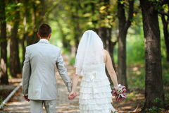 Bride and groom walking away in summer park outdoors Royalty Free Stock Photo