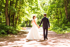 Bride and groom walking away  in summer park outdoors Royalty Free Stock Photography