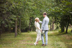 Bride and groom walking away in summer park outdoors Royalty Free Stock Image