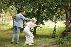Bride and groom walking away in summer park outdoors Stock Photo