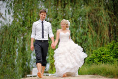 Bride and groom walking barefoot on the beach Stock Photos