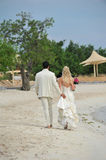 Bride and groom walking on beach Stock Images