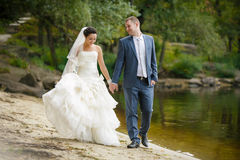 Bride and groom are walking on the beach Stock Photo