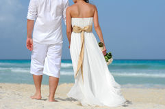 Bride and groom walking on the beach Stock Images