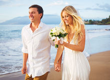 Bride and Groom Walking on Beautiful Tropical Beach at Sunset, R Royalty Free Stock Image