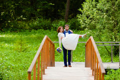 Bride and groom walking on a bridge Stock Images