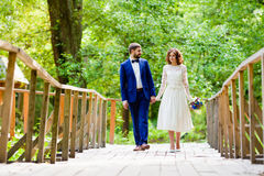 Bride and groom walking on a bridge Royalty Free Stock Photography