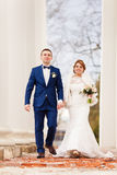 The bride and groom are walking between the columns Royalty Free Stock Image