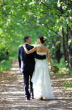 Bride and Groom Walking into Distance. A portrait of a bride in a traditional white wedding dress. She is walking down a country lane with her new husband arm in Royalty Free Stock Photos