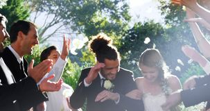 Bride and groom walking down while guests toss petals 4K 4k