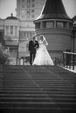 Bride and groom walking down the stairs at city Royalty Free Stock Images