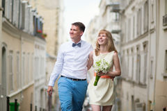 Bride and groom walking down the street in Paris Royalty Free Stock Photography