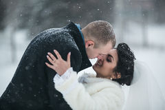 Bride and groom walking on the European city in the snow Royalty Free Stock Images