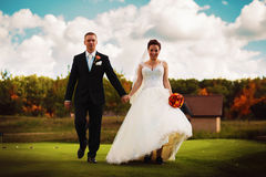 Bride and groom walking on golf field Stock Images