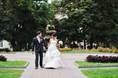Bride and groom walking in a green park Royalty Free Stock Image