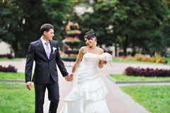 Bride and groom walking in a green park Stock Photography