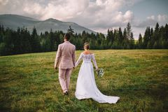 Bride and groom walking hand by hand stock image