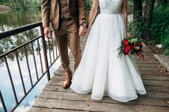 Bride and groom are walking and holding hands. Bride and groom across the bridge are walking and holding hands Stock Photo