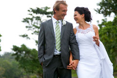 Bride and Groom walking holding hands and laughing Royalty Free Stock Image