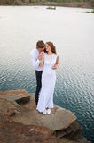 Bride and groom walking near beautiful lake. Wedding couple in love Stock Images