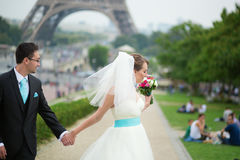 Bride and groom walking near the Eiffel tower Royalty Free Stock Photo