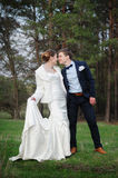 Bride and groom walking near pine forest on the wedding day Royalty Free Stock Image