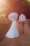 Bride and groom in walking off into the sunset royalty free stock photos