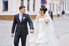 Bride and groom walking in an old town Stock Photos