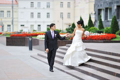 Bride and groom walking in an old town Royalty Free Stock Photography