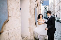 Portrait of a romantic beautiful couple traveler walking in the. Bride and groom walking through the old town Stock Images