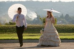 Bride and groom walking outside in sun with umbrel Royalty Free Stock Photography