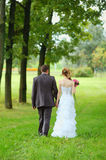 Bride and groom walking in the park Stock Image